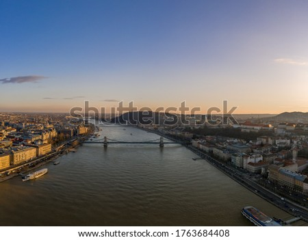 Aerial drone shot of Danube river with chain bridge and Buda Castle in Budapest in Sunset hour in winter #1763684408