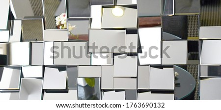 Mirror with foursquare in wall, decoration and reflection. Abstract glass background. Polygonal surface. Closeup. Texture.