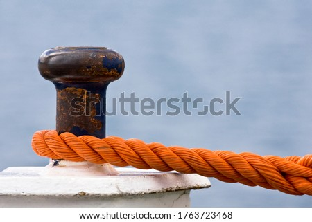 Rusty bollard with knotted mooring rope. Outdoor picture of nautical equipment taken on a vessel.