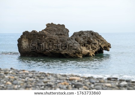 Big rock in the middle of the ocean under a blue sky in Nerja in Spain. #1763733860