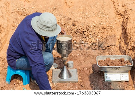 Worker using equipment for testing laboratory field density test sand cone method and soil density test of road under the construction.Soil field density test sand cone method calculation . Royalty-Free Stock Photo #1763803067