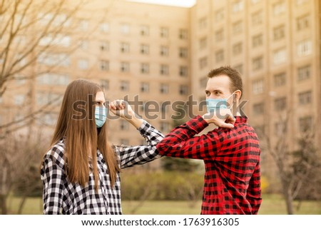 Young couple wearing face mask outdoors say hello with elbows outdoors. No hugs, no kisses, no shake hands. Friends shaking elbows outdoors. Greeting with elbows. #1763916305