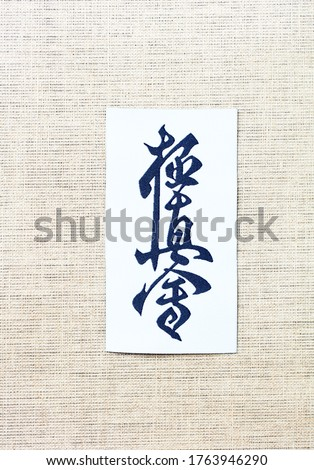 """Calligraphy - Kyokushinkai karate symbol on linen background.  """"Kyokushin"""" is a style of stand-up, full contact karate and is Japanese for """"the ultimate truth"""". Top view. Copy space.  Royalty-Free Stock Photo #1763946290"""