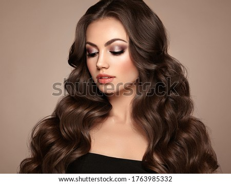 Brunette Girl with Long Healthy and Shiny Curly Hair. Care and Beauty. Beautiful Model Woman with Wavy Hairstyle. Make-Up and Black Dress #1763985332