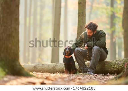 Hound as a hunting dog together with a hunter or forester take a break in the forest Royalty-Free Stock Photo #1764022103