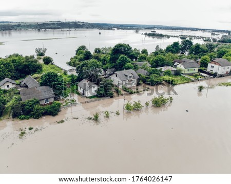 Climate change and the effects of global warming. Flooded houses, streets, farms and fields after heavy rains. Environmental natural disaster. Concept of global catastrophes in the world Royalty-Free Stock Photo #1764026147