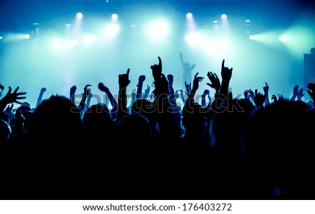 silhouettes of concert crowd in front of bright stage lights #176403272