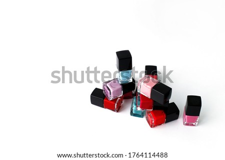 Multi-colored nail polish on a white background. Bright bottles with nail polish. Means for manicure.