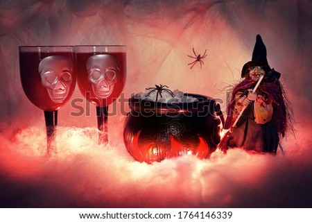 Halloween figure of a witch with a broom on a lighted smoky background of cobwebs, standing next to a burning witch's cauldron filled with food and snacks, on which a spider crawls, next to two creepy Royalty-Free Stock Photo #1764146339