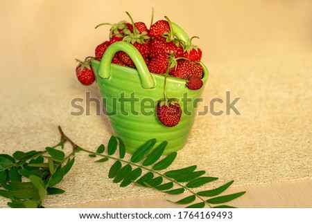 Red strawberries in a green porcelain basket with branch #1764169493