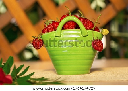 Red strawberries in a green porcelain basket with branch on a table. Background wooden fence #1764174929