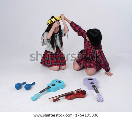 Elder sister put Tambourine on head of Younger sister,funny time.Ukulele,violin and Maracas on ground floor.doing activity together #1764195338