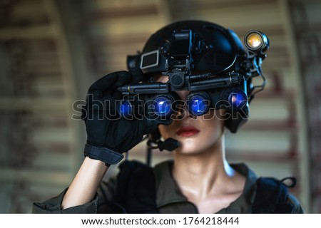 Portrait of female modern army special forces soldier, anti terrorist squad fighter, elite commando warrior using four-eyed night vision goggles in dark background Royalty-Free Stock Photo #1764218444