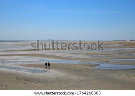 High angel panoramic view of the shoreline during low tide on Terschelling Island with tide pools and sand banks on a sunny and clear day, two people taking a walk on otherwise empty beach Royalty-Free Stock Photo #1764260303