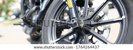 Close-up of rear wheel of motorcycle in city street. Transport for ride. Black and yellow design. Freedom and adventure. Bikes gear. Technology and vehicle concept #1764264437