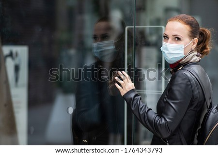 Sad woman at the entrance to a closed clothing store in a shopping center in a mask on her face. Closed store, shop because of Quarantine, coronavirus, covid-19 Royalty-Free Stock Photo #1764343793