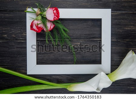 top view of an empty picture frame with red roses with fennel and white color calla lilies on dark wooden background with copy space