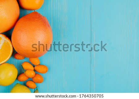 top view of citrus fruits as orange lemon tangerine and kumquats on left side and blue background with copy space #1764350705