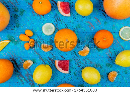 top view of pattern of citrus fruits as orange lemon tangerine kumquat grapefruit on blue background #1764351080