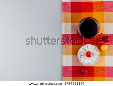 top view of rice cake with cream cheese and fresh ripe rainier cherries and a glass of cherry juice on plaid napkin on grey background with copy space #1764351134