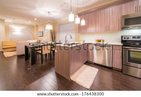 Outlook, panorama at the luxury and nicely decorated modern kitchen and dining table and living room at the back. Interior design of a brand new house. #176438300