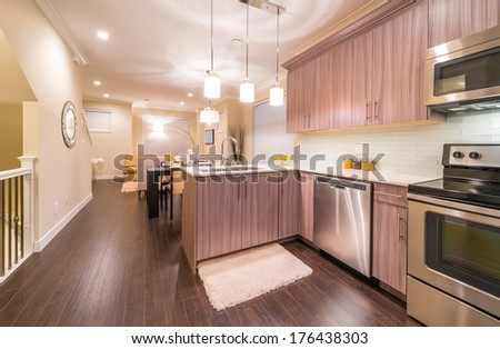 Outlook, panorama at the luxury and nicely decorated modern kitchen and dining table and living room at the back. Interior design of a brand new house. #176438303