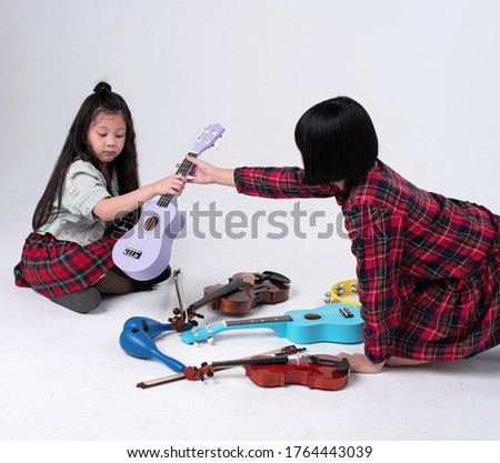 Two little girls sitting on ground floor.sending purple ukulele together,prepare for practice,plenty of acoustic instrument around #1764443039