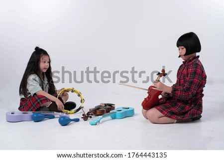 Two little girls sitting on ground floor.Beside ukulele,violin,Maracas and Tambourine,doing activity together #1764443135