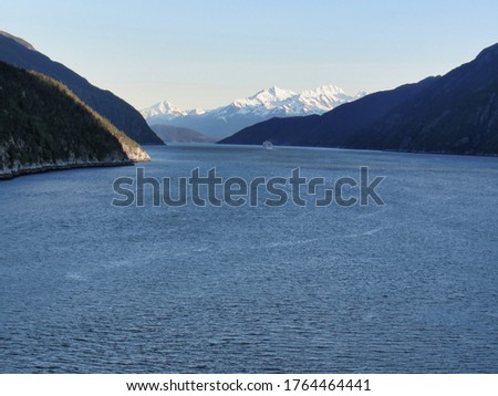 Beautiful view of the inside passage, Alaska. Blue ocean, snow capped mountains and cruise ship on the horizon.