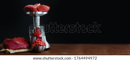 The meat is put in the meat grinder and minced  comes out of it, next to it lies a huge piece of beef tenderloin. Minced meat, meat delicacies, fresh craft food. Elongated panoramic image #1764494972