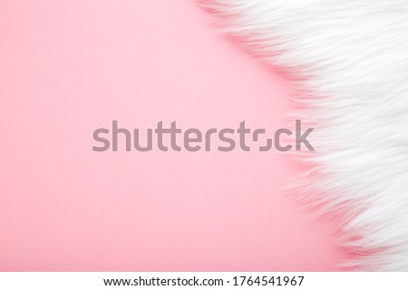 Light, white fur on pastel pink table background. Empty place for text.  Royalty-Free Stock Photo #1764541967