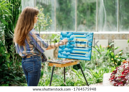 Young beautiful girl in work clothes draws a picture while with an easel in the botanical garden. Girl enjoy solitude with nature.