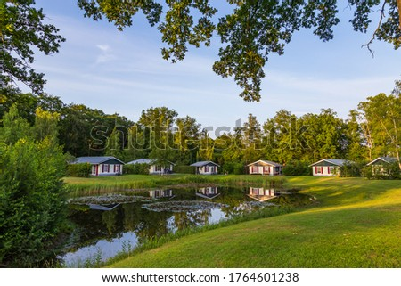 Row of colorful wooden vacation home reflected in a pond at recreation park in the middle of nature in the Netherlands Royalty-Free Stock Photo #1764601238