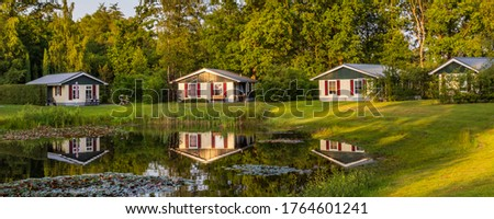 Panorama with row of colorful wooden vacation home reflected in a pond at recreation park in the middle of nature in the Netherlands Royalty-Free Stock Photo #1764601241