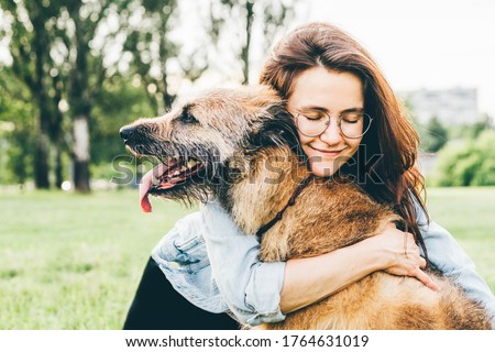 Women hugging dog in the summer park. Cheerful lady with long dark hair in blue jacket hugs and strokes friendly old dog sitting on lush green meadow of public garden on nice day.  #1764631019