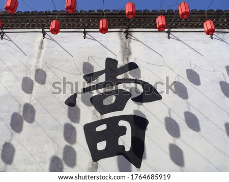Chinese ancient pawnshop with Chinese character of pawnshop on white wall in Shaoxing, Zhejiang Province (the Chinese character on the wall means the act of pawn, also the ordinary name for pawnshop)