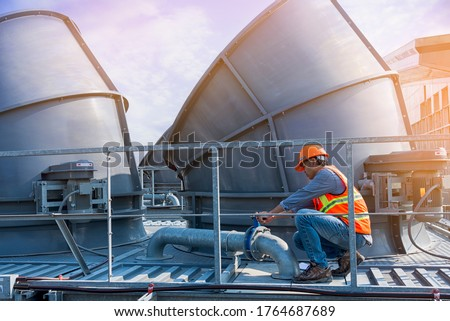 worker open valve of cooling tower on blue sky background.worker opening butterfly valve on top of cooling Tower. engineer check valve on cooling tower. #1764687689