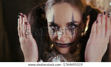 Easy Halloween Makeup. Woman covers her face with her hands. The girl with the picture on her face. #1764695519