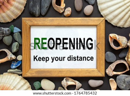 Wooden picture frame with inscription 'reopening keep your distance' on beautiful black background. Sea stones and seashells. Concept.