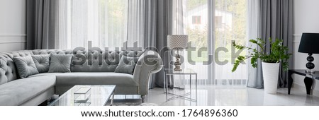 Panorama of glamour style living room with quilted corner sofa and glass coffee table Royalty-Free Stock Photo #1764896360
