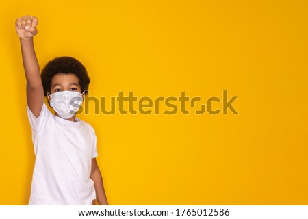 Portrait of little afro boy with medical face mask looking at camera. Child wearing protective mask from virus . Coronavirus and pandemic concept. Kid in hero pose with mask Royalty-Free Stock Photo #1765012586