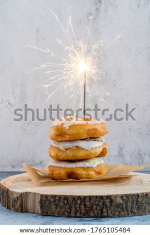 Three donuts with white icing sugar and sparkler on baking paper and wood. Festive picture. Selective focus. Concrete background.