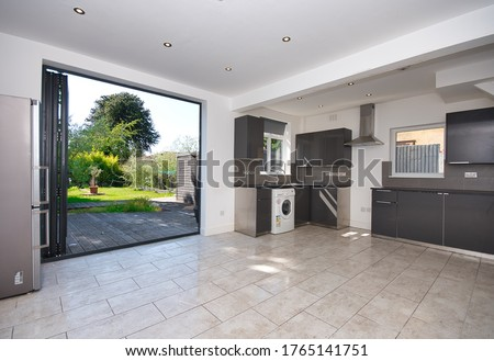 Contemporary Kitchen with bi folding aluminium doors leading to garden decking UK Royalty-Free Stock Photo #1765141751