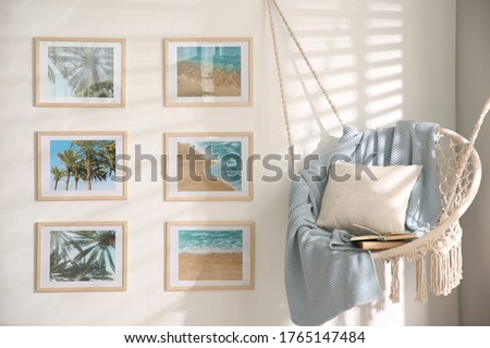 Different pictures on wall and hanging chair in room. Artworks in interior design