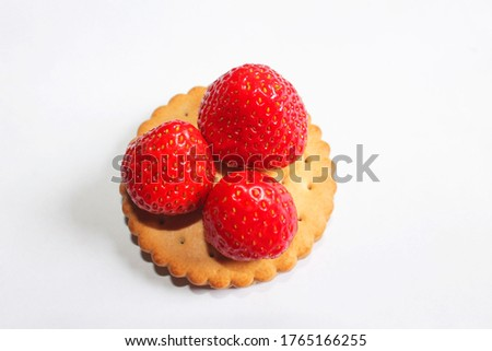 A round brown cookie with a wavy edge and small holes lies on a white surface. Three red strawberries of different sizes lie on cookies. Dessert. Close-up, top view. #1765166255