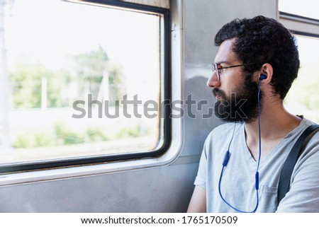 A young man with glasses, headphones and a beard sits in a train car and listens to music. Tourism and travel. Close-up. #1765170509