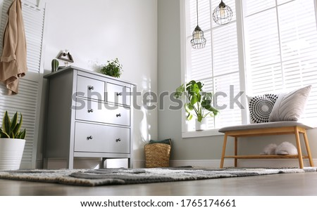 Grey chest of drawers in stylish room interior, low angle view Royalty-Free Stock Photo #1765174661