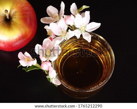 Natural Apple juice in a glass with white apple flowers and an apple on a black background closeup, top view. Bright romantic picture with a drink and blooming