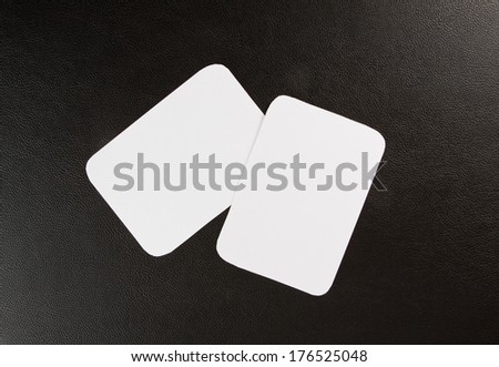 blank business cards with rounded corners on a black leather background