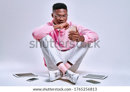 Guy sitting on the floor and working in smartphone on white background. Many devices around. Copy space